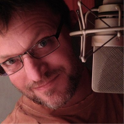 Voiceover actor Steve Blum peaking out from behind the mic