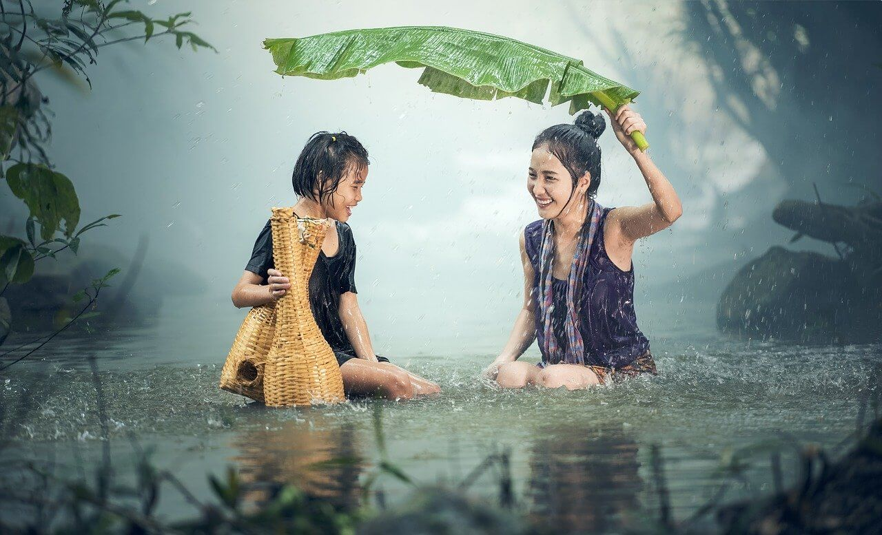 Woman and Little Girl trusting in the power of authenticity by laughing in the rain