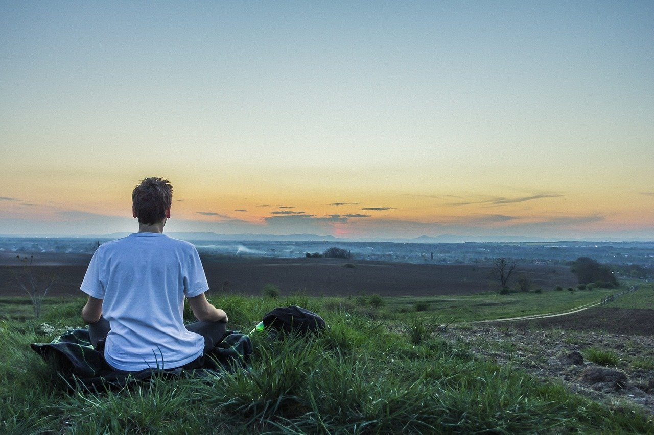 Person recalibrating by meditating in field