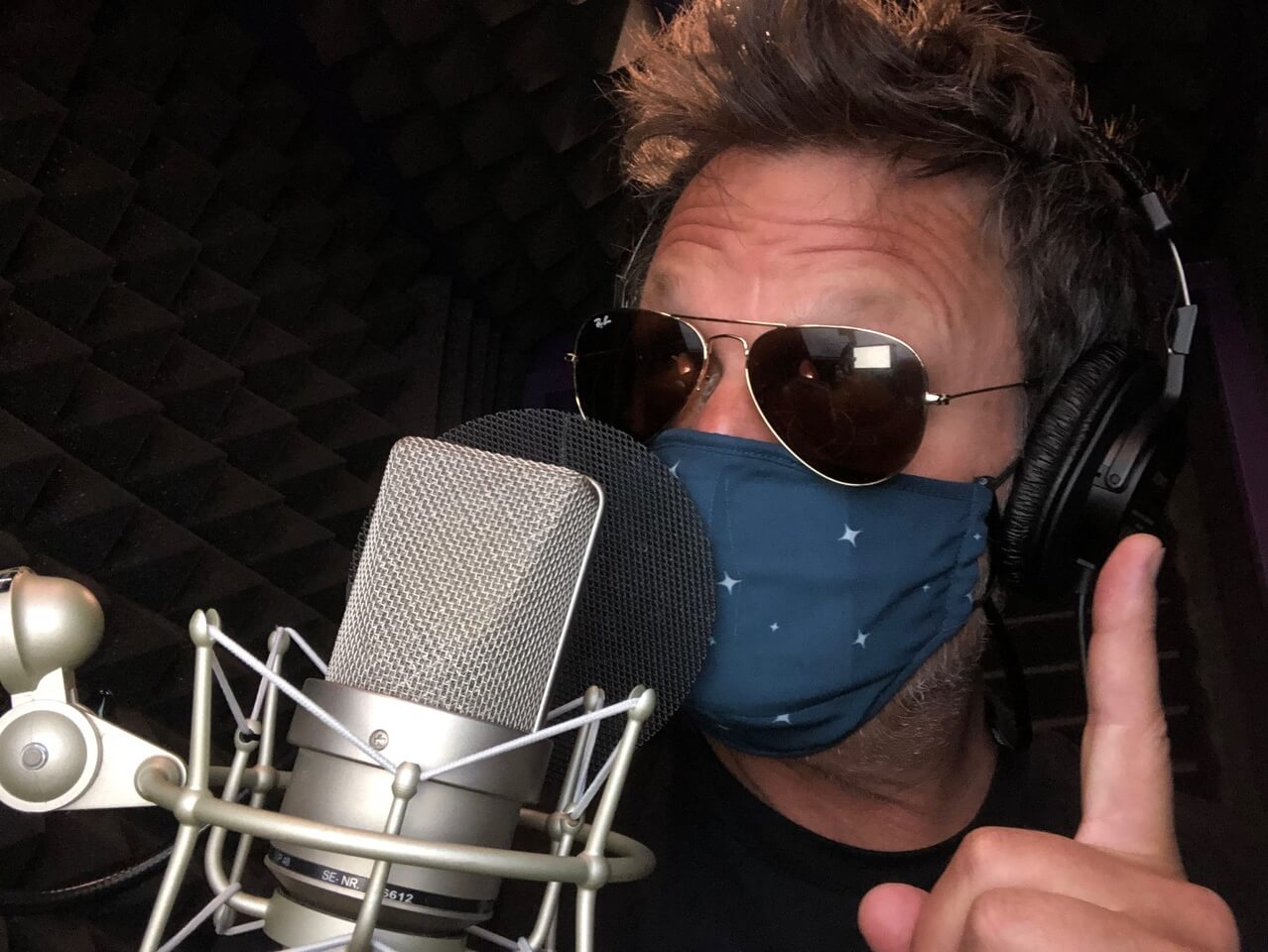50 Classes-Beyond the Vision_Steve Blum at the mic with sunglasses and a mask on